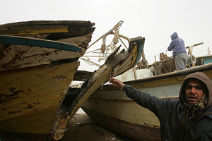 Palestinian man pointing at a broken fishing boad